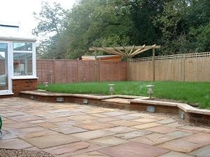 Indian-Sandstone-patio-with-raised-lawn-deck-and-fan-effect-pergola