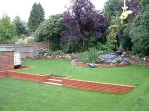 Multi-terraced-lawn-with-retaining-walls-and-a-semi-circle-raised-pond